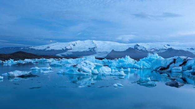 Jokulsarlon, lagoa glaciar na islândia à noite com gelo flutuando na água.