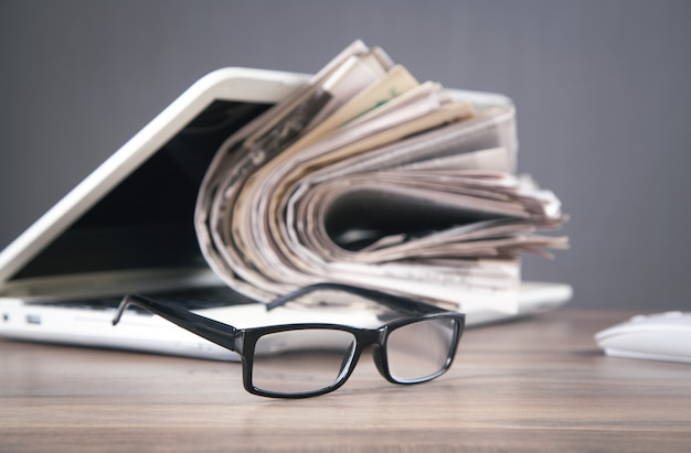 Jornais, computador, óculos na mesa de madeira.