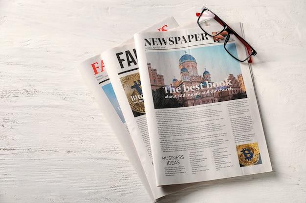 Jornais e copos na mesa de madeira branca