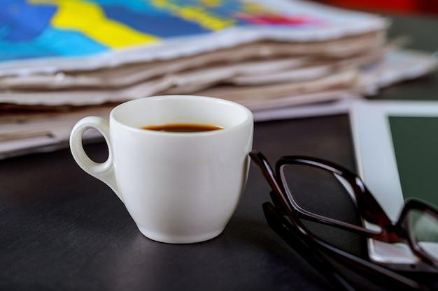 Jornais e xícara de café, óculos de leitura e bloco de notas
