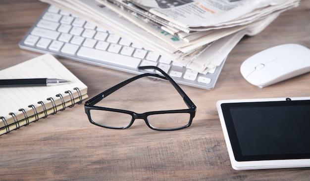 Jornais, teclado de computador, óculos na mesa de madeira.