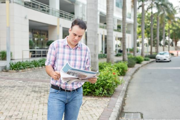 Jornal de leitura de homem sério na rua
