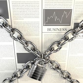 Jornal de negócios e cadeado acorrentado isolado no fundo branco.
