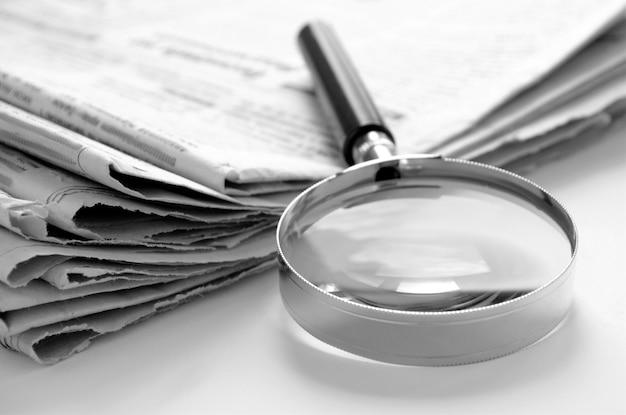 Jornal diário e uma lupa para encontrar notícias