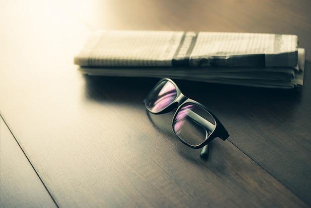 Jornal e óculos de leitura no jornal de negócios da mesa de negócios.