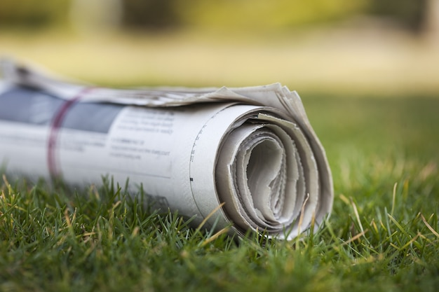 Jornal sobre fundo de grama verde ao ar livre