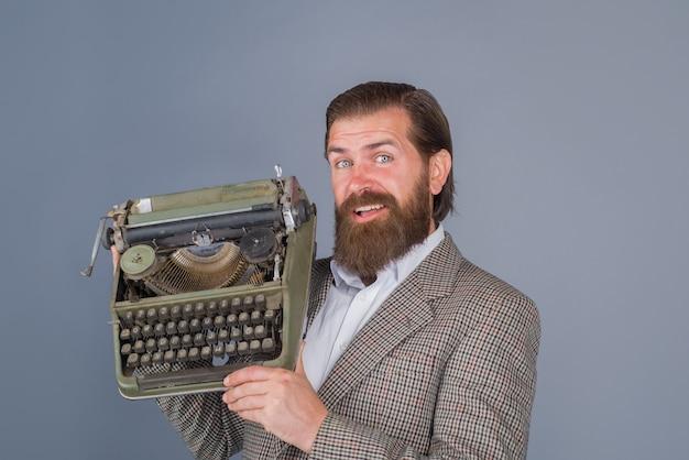 Jornalista barbudo com máquina de escrever segura uma máquina de escrever antiguidades, antigo secretário do jornalista seo negócios