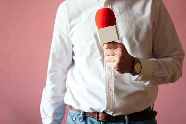 Jornalista com microfone na mão na parede rosa