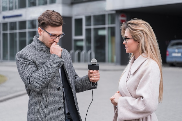 Jornalista de vista lateral entrevistando mulher