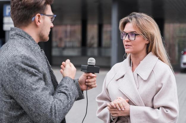 Jornalista de vista lateral fazendo entrevista