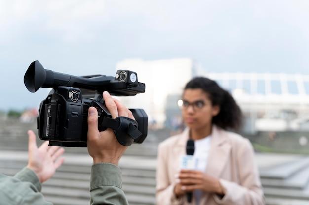Jornalista feminina contando as notícias do lado de fora