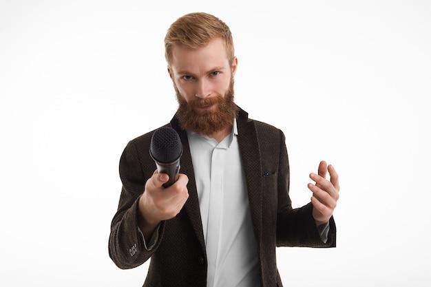 Jornalista masculino barbudo elegante vestido com uma jaqueta elegante apontando o microfone na frente durante a entrevista, tendo olhar desconfiado.