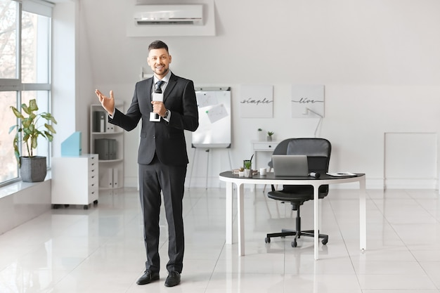 Jornalista masculino com microfone dentro de casa