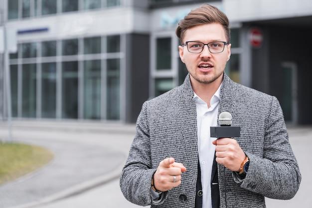 Jornalista masculino de alto ângulo apontando