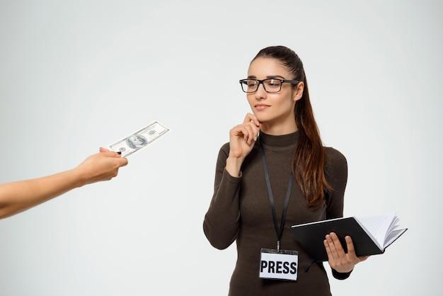 Jornalista mulher tentadora subornar, olhar para o dinheiro