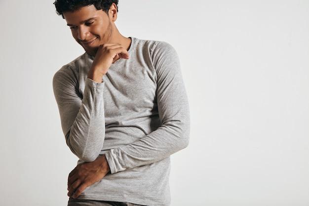 Jouyful sorridente jovem latino em manga comprida cinza em branco olha para o lado e se posiciona na frente da parede branca
