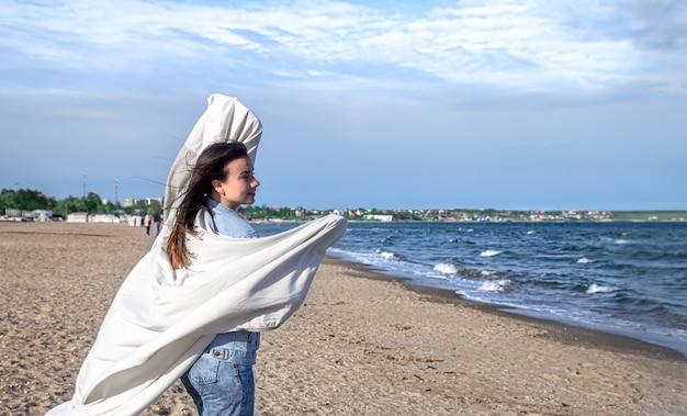 Jovem à beira-mar se diverte segurando um grande lençol ao vento, um estilo de vida livre.