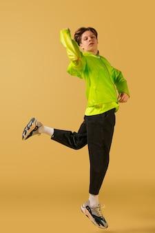 Jovem à moda antiga dançando isolado em um fundo amarelo