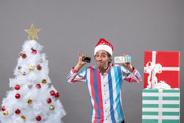 Jovem abençoado com um cartão e uma passagem ao redor da árvore de natal e presentes