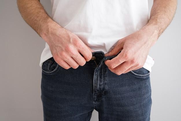 Jovem abotoando a calça jeans em um fundo cinza, close-up.