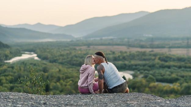 Jovem abraça a namorada no pico da montanha ao pôr do sol