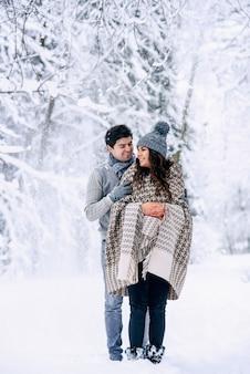 Jovem abraça com ternura sua linda esposa grávida coberta por um cobertor quente com neve
