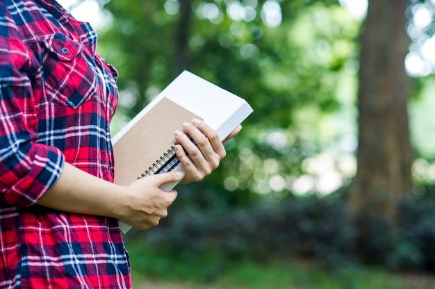 Jovem abraça o livro na selva verde