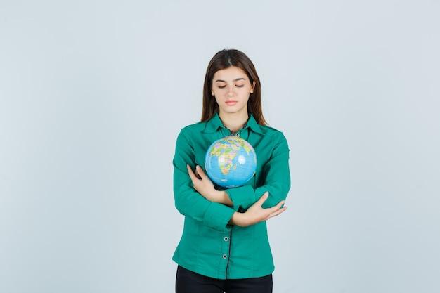 Jovem, abraçando o globo terrestre na camisa e olhando cuidadosa, vista frontal.