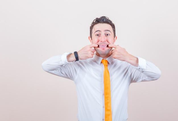 Jovem abrindo a boca com os dedos, mostrando a língua na camisa e parecendo engraçado