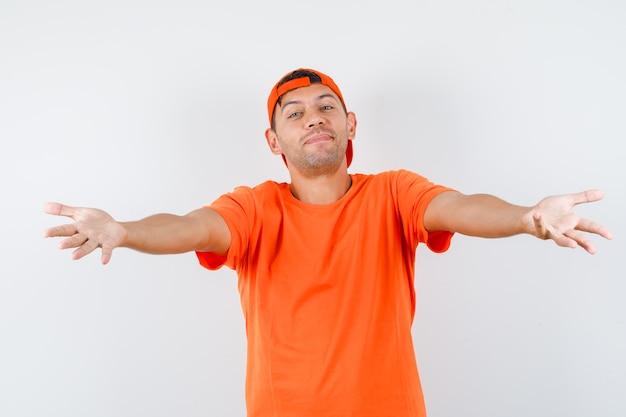 Jovem abrindo os braços para um abraço com camiseta laranja e boné, parecendo gentil