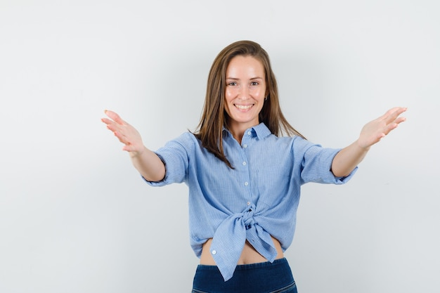 Jovem abrindo os braços para um abraço na camisa azul, calça e parecendo feliz.