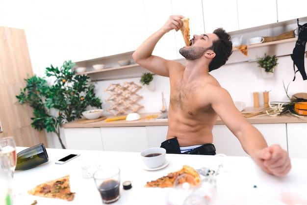 Jovem acorda e tomando café da manhã depois da festa