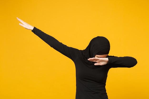 Jovem adolescente árabe muçulmana com roupas pretas de hijab, fazendo o gesto de dança com as mãos isoladas no retrato de parede amarela. conceito de estilo de vida religioso de pessoas.