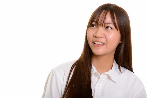 Jovem adolescente asiática feliz sorrindo e pensando