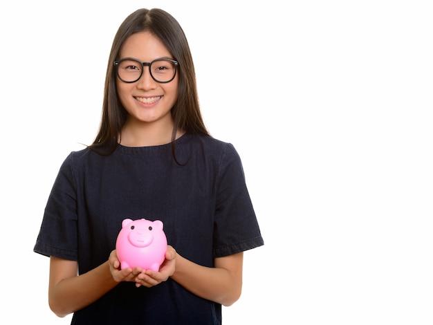 Jovem adolescente asiática feliz sorrindo e segurando o cofrinho