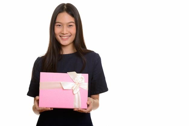 Jovem adolescente asiática feliz sorrindo e segurando uma caixa de presente