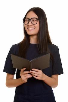 Jovem adolescente asiática feliz sorrindo enquanto segura um livro