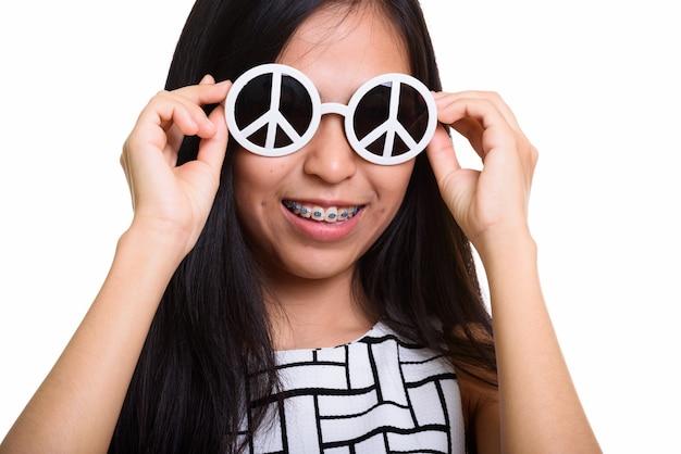 Jovem adolescente asiática feliz sorrindo enquanto usava óculos escuros