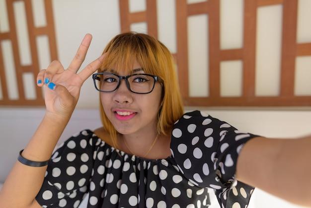 Jovem adolescente asiática relaxando em casa