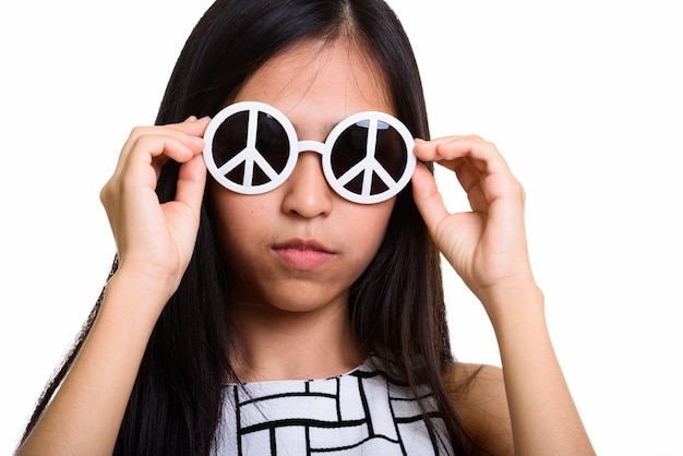 Jovem adolescente asiática segurando óculos escuros e óculos de sol da paz