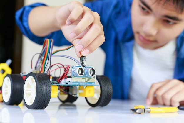 Jovem adolescente asiático conectando energia e cabo de sinal ao chip sensor da oficina de carros de brinquedo.