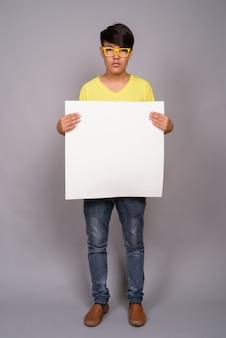 Jovem adolescente asiático vestindo camisa amarela e óculos contra parede cinza