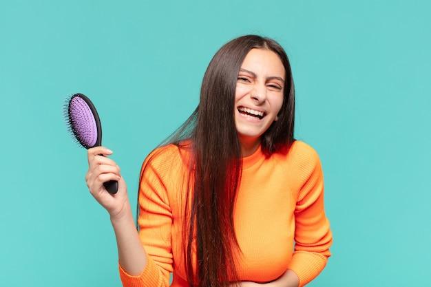 Jovem adolescente bonita. expressão feliz e surpresa. conceito de escova de cabelo