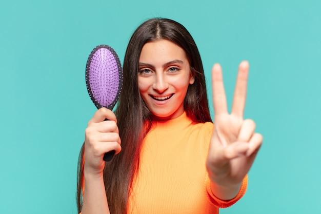 Jovem adolescente bonita fazendo sinal de vitória e segurando a escova