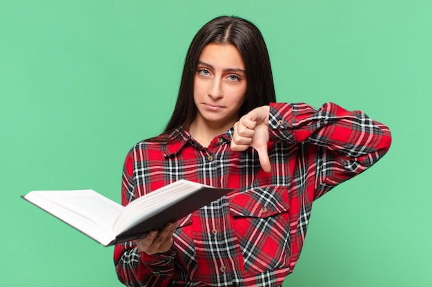Jovem adolescente bonita lendo um livro e dando o polegar para baixo