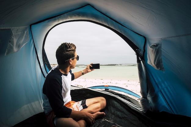 Jovem adolescente bonito acampamento diretamente na praia branca no paraíso tropical, coloque ilhas da porta da tenda tire uma foto com o telefone para a água verde incrível casa