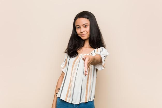 Jovem adolescente bonito, esticando a mão na câmera em gesto de saudação.