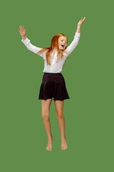 Jovem adolescente caucasiana feliz pulando no ar, isolado no fundo verde do estúdio.