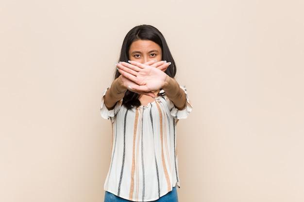 Jovem adolescente chinês bonito jovem loira vestindo um casaco contra uma parede rosa, fazendo um gesto de negação