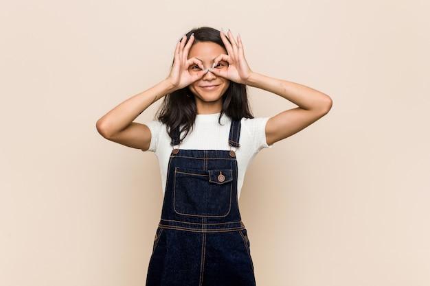 Jovem adolescente chinês bonito jovem loira vestindo um casaco contra uma parede rosa mostrando sinal bem sobre os olhos